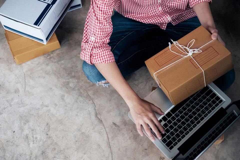 Persona sosteniendo una caja de cartón de un producto a la vez que utiliza un portátil