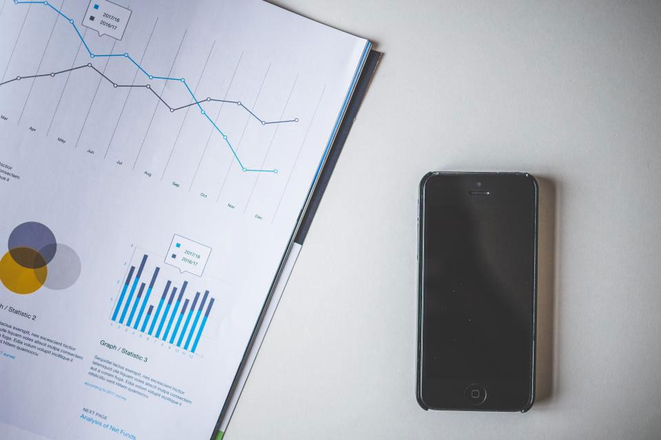 Un teléfono móvil a la derecha de una hoja con estadísticas y graficos