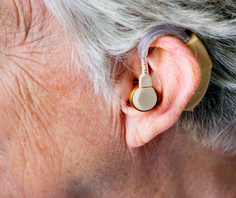 Paciente llevando un audífono en la oreja
