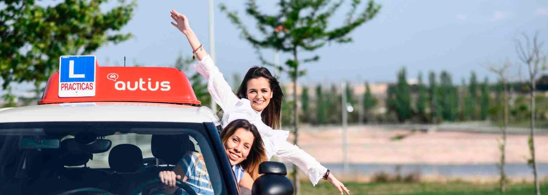 Dos chicas felices en las ventanas de un coche de autoescuela Autius
