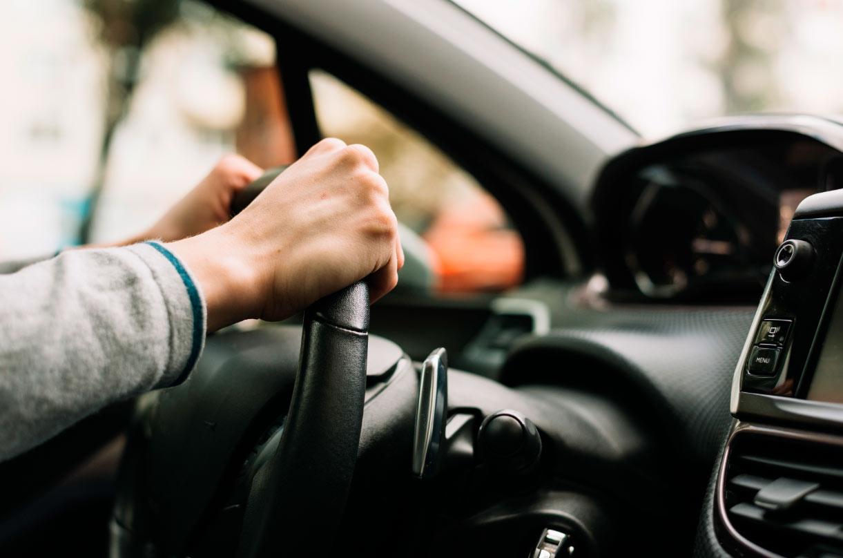 Manos agarrando un volante de coche con firmeza