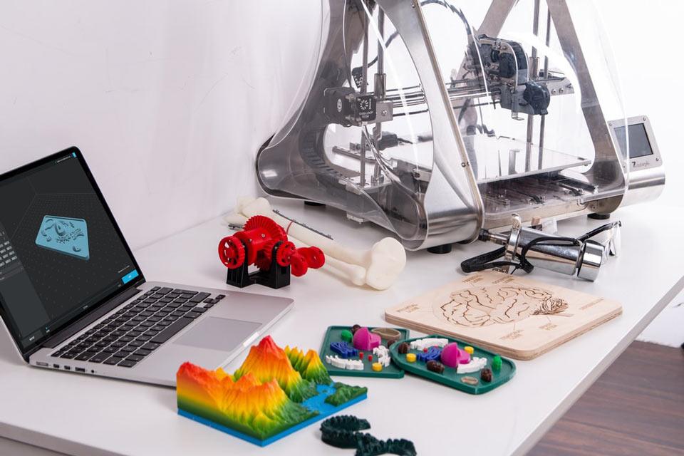 Escritorio con ordenador portátil y una impresora 3D